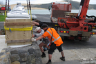 Foundryman Joe Crowther (left), Opo committee member George Goodhew and hiab operator Thomas Parsons ease the sculpture and its three-tonne granite base into position. PHOTO / PETER DE GRAAF