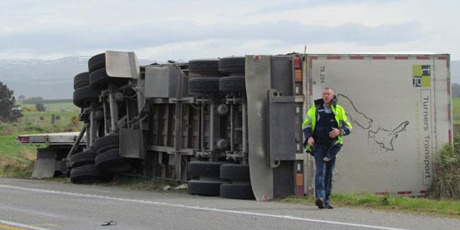 A truck lies facing the opposite way it was heading on State Highway 1 north of Dunedin, after being blown over. Photo / ODT
