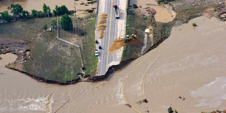 A road crew works on a stretch of highway washed out by flooding along the South Platte River. Photo / AP