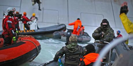 A Russian Coast guard officer is seen pointing a gun at a Greenpeace International activist as five activists attempt to climb the Prirazlomnaya.