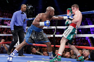 Floyd Mayweather Jr. throws a jab against Canelo Alvarez against the ropes in the eighth round during a 152-pound title fight, Saturday, Sept. 14, 2013, in Las Vegas. (AP Photo/Eric Jamison)
