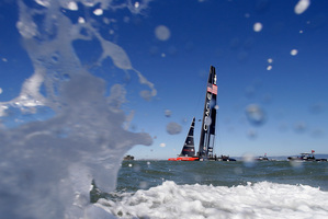 Oracle Team USA makes its way along the waterfront after winning the ninth race. Photo / AP