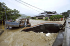An overturned sightseeing boat is stuck by a bridge after the Katsura River was overflooded by torrential rains in the popular tourist destination of Kyoto. Photo / AP