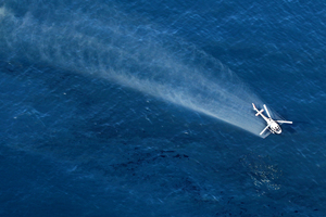 A helicopter sprays dispersant after the Rena oil spill.