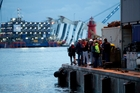 Workers gather before the operation to refloat the Costa Concordia, seen in the background. Photo / AP