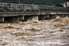 Muddy water of the Katsura river runs under a bridge in Kyoto as torrential rain hit western Japan. Photo / AFP
