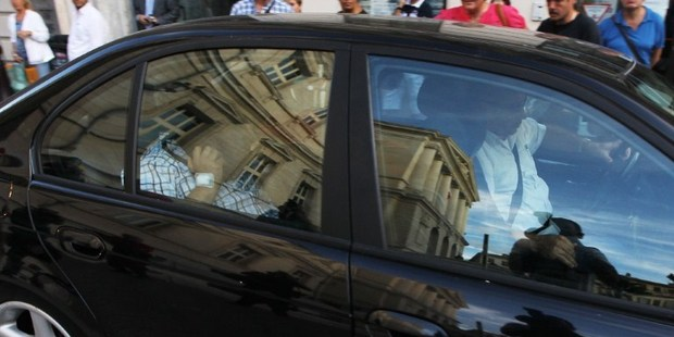 Stephan Turk (back seat), who killed a thief who had broken into his jewelry store, hides his face as he leaves the courthouse in Nice, on September 13, 2013. Photo / AFP