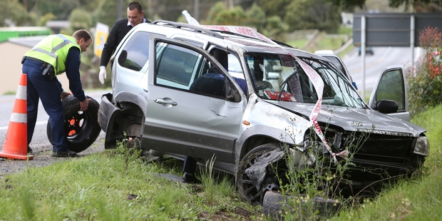 Police with the crashed vehicle south of Whangarei. Photo / Michael Cunningham