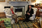 The Queen, wearing a Balmoral tartan skirt and surrounded by family photos, meets Prime Minister John Key in her Balmoral sitting room. Photo / Claire Trevett