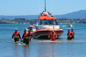 TWL 31Jan13 - VOLUNTEERS: Six members of Newmont's Mines Rescue Unit wade ashore at Anzac Bay after spending Tuesday morning searching the Matakana shoreline for missing Katikati man, Tim Mair 5