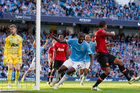 City's Yaya Toure, centre, celebrates after scoring against United. Photo / AP