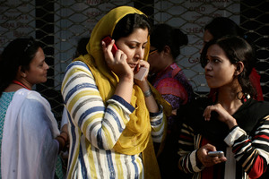 A Pakistani woman speaks on her mobile phone after rushing out of her apartment following a major earthquake that struck Baluchistan province in southwest Pakistan. Photo / AP