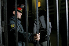 A Russian police officer guards an entrance of the Russian Investigative Committee office where Greenpeace activists were taken for questioning, in Murmansk, Russia. Photo / AP