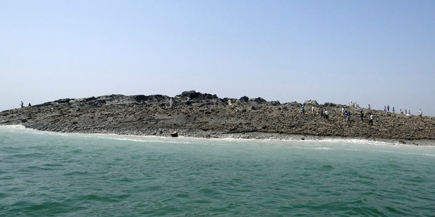People walk on an island that reportedly emerged off the Gwadar coastline in the Arabian Sea. Photo / AP