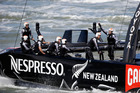 Emirates Team New Zealand sails near the waterfront after coming in second to Oracle Team USA during the final race. Photo / AP