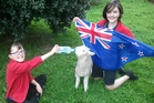 Heidi (left) and Abigail Hurley give a patriotic feed to woolly mate Dean Baakaa.
