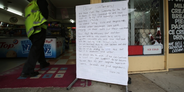 The Maungatapu Superette's owners are upset the stationers next door are selling the same products and a large sign at their front door asks customers for support. Photo / Joel Ford