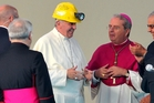 Pope Francis, with Cagliari Archbishop Arrigo Miglio, wears the helmet he was given by a coalminer during his visit to the capital of Sardinia. Photo / AP