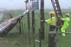 Firefighters remove a sign that was damaged by strong winds and rain that hit Whitianga, Coromandel.