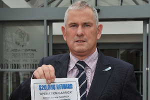 Detective Sergeant Derek Shaw with a copy of a reward poster offering $20,000 for information on the disappearance of Simon James Garrick. Photo / Gregor Richardson