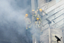 Firefighters rescued four people, including two from the roof, while battling the blaze in the Commerce St apartment building. Photo / Shirley Campbell