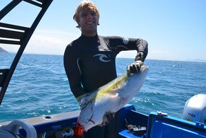 Steve Clark with the 9kg kingfish half he was left with after spearing it, fighting it in the water for 2 minutes and then losing half of it to a shark. Photo / Amy Fletcher