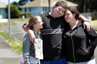 Newspaper runner Richard Frederick is comforted by his niece, Jessemine-Grace, and sister, Amanda, yesterday, just hours after being attacked. Photo / Stuart Munro