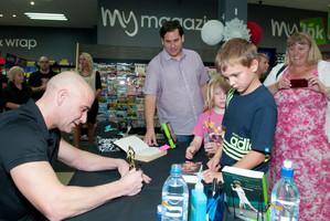 Andre Agassi signs a trophy brought by Ben and Petra Curd-McCullough at a book signing session in the Eastgate Mall, Christchurch. Photo / David Alexander