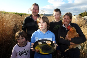 The Youthed family with their chicken, Blondie, who layed a double shelled egg. Photo / Paul Taylor
