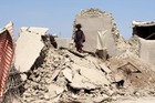 A Pakistani girl walks on the rubble of a house destroyed following an earthquake in Labach, the remote district of Awaran in Baluchistan province, Pakistan. Photo / AP