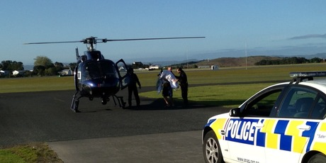 Gus is bundled in a blanket to a helicopter which has flown him to Auckland for surgery this morning. Photo / NZ Police
