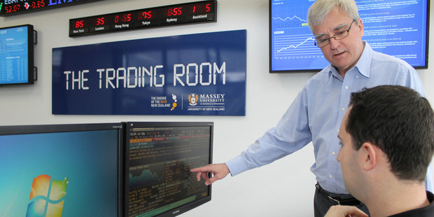 Professor Russell Gregory-Allen discusses information with postgraduate student Sam Weir in Massey University's Albany campus trading room.
