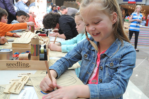 A young crafter at the Seedling crafts stand at a Westfield mall.