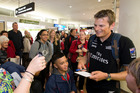 Dean Barker from Team New Zealand stands with fans after they were welcomed home at Auckland International Airport. Photo / Greg Bowker