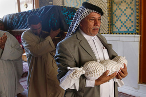 Mahmoud Abdel-Rahman carries the body of his infant grandson, Latif, who was killed in a car bomb attack. Photo / AP