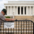 A US Park Police officer watches at left as a National Park Service employee posts a sign on a barricade closing access to the Lincoln Memorial in Washington. Photo / AP