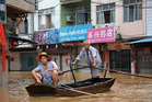 Residents paddle a boat in flood waters triggered torrential rains from typhoon Utor on a street in Fengkai in south China's Guangdong province.Photo / AP