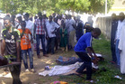 Rescue workers and family members gather to identify the victims of the Boko Haram attack. Photo / AP
