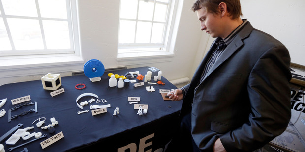 Aaron Kemmer, CEO and co-founder of Made in Space, looks through some items made with the company's 3D printer which will eventually be used in space. Photo / AP