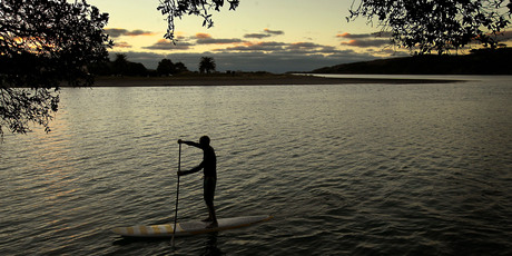 A paddleboarder glides across the calm waters of Raglan Harbour as night falls. Photo / Alan Gibson