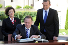 New Zealand Prime Minister John Key signs the visitors book, watched by the Australian Prime Minister Tony Abbott, at the Australian War Memorial in Canberra. Photo / SNPA