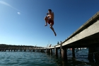 As temperatures hit the high 30s in Sydney yesterday, people tried to cool off. A man jumps into the water at Balmoral Beach. Photo / Getty Images
