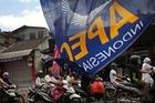Motorcyclists make their way through a street decorated with banners for the Apec meetings in Bali. Photo / AP