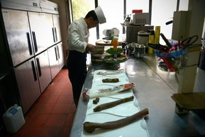 A cook preparing a dish of animal penis in the kitchen.Photo / AFP
