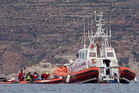 Italian Coast Guard personnel recover a body bag on their patrol boat in Lampedusa island. Photo / AP