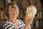 Neuropsychologist Jenni Ogden, in her library on Great Barrier Island, with a model of a brain. Photo / Greg Bowker