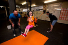 Matt Piggin helps his daughter Riley on the rings as Crossfit owner Paul Davies works with Piper. Photo / Dean Purcell