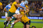 Argentina's Patricio Albacete, center, is tackled by Australia's Benn Robinson, left, and Rob Simmons during their Rugby Championship match in Rosario, Argentina. Photo / AP