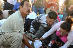 Injured people are treated after an out of control monster truck plowed through a crowd of spectators at a Mexican air show in the city of Chihuahua, Mexico. Photo / AP