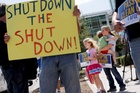 As the federal government shutdown continues, Tory Anderson, right, with her kids Audrey, 7, and Kai, 3, of Goodyear, Ariz., join others as they rally. Photo / AP
